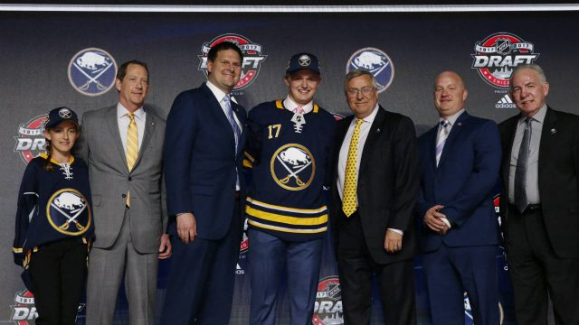 Casey-Mittelstadt,-center,-holds-a-Buffalo-Sabres-jersey-after-being-selected-by-the-team-in-the-first-round-of-the-NHL-hockey-draft,-Friday,-June-23,-2017,-in-Chicago.-(Nam-Y.-Huh/AP)