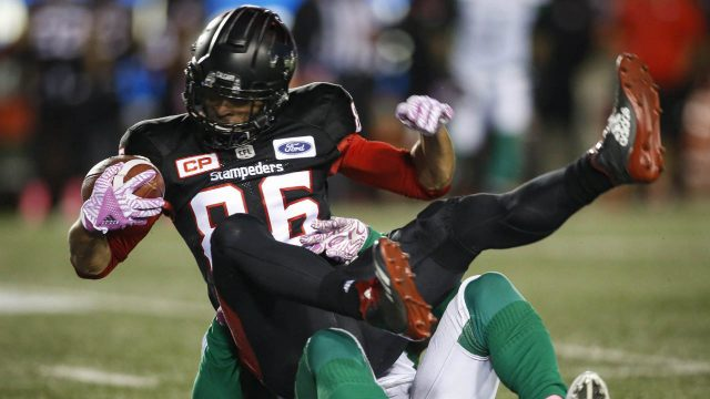 Saskatchewan-Roughriders'-Samuel-Eguavoen,-bottom,-tackles-Calgary-Stampeders'-Anthony-Parker-during-first-half-CFL-football-action-in-Calgary,-Friday,-Oct.-20,-2017.-(Jeff-McIntosh/CP)