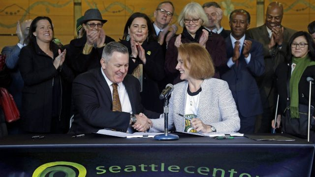 Seattle-Mayor-Jenny-Durkan,-right,-shakes-hands-with-Los-Angeles-based-Oak-View-Group-CEO-Tim-Leiweke-after-they-signed-an-agreement-to-renovate-KeyArena,-Wednesday,-Dec.-6,-2017,-in-Seattle.-Durkan-said-that-the-deal-is-the-best-path-right-now-for-Seattle-to-get-an-NHL-team-and-bring-back-the-SuperSonics.-(Elaine-Thompson/AP)