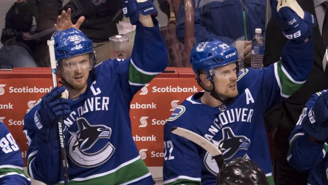 Vancouver-Canucks-Henrik-(33)-and-Daniel-Sedin-(22)-wave-to-the-crowd-during-a-standing-ovation-during-third-period-NHL-action-against-the-Las-Vegas-Knights-at-Rogers-Arena-in-Vancouver,-Tuesday,-April-3,-2018.-The-Sedin-brothers-announced-on-Monday-that-they-will-retire-following-the-teams-last-game-of-the-season-Saturday-night.-(Jonathan-Hayward/CP)