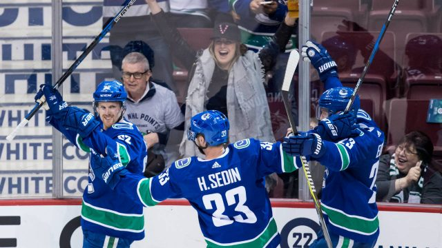 Vancouver-Canucks-players,-from-left-to-right,-Daniel-Sedin,-Henrik-Sedin-and-Alexander-Edler,-all-of-Sweden,-celebrate-Daniel-Sedin's-goal-during-second-period-NHL-hockey-action-against-the-Arizona-Coyotes,-in-Vancouver-on-Thursday,-April-5,-2018.-(Darryl-Dyck/CP)