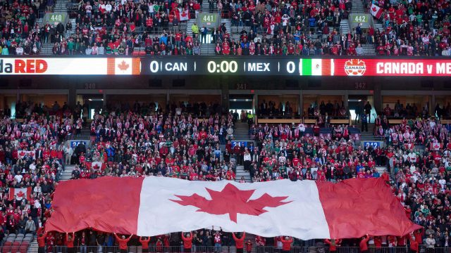 A-large-Canadian-flag-is-held-up-by-fans-before-Canada-and-Mexico-play-a-FIFA-World-Cup-qualifying-soccer-match-in-Vancouver-on-March-25,-2016.-The-bid-group-hoping-to-bring-the-2026-World-Cup-to-North-America-has-unveiled-its-23-candidate-cities-but-not-without-a-crack-to-its-much-ballyhooed-unity-theme.The-list-of-potential-host-cities-includes-Edmonton,-Montreal-and-Toronto.-But-Vancouver-joined-Chicago-and-Minneapolis-in-dropping-out-at-the-last-minute-over-concerns-about-FIFA's-demands.-(Darryl-Dyck/CP)